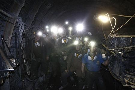 A group of miners pose for a photograph inside of an excavation corridor at JSW's Zofiowka coal mine in Jastrzebie Zdroj