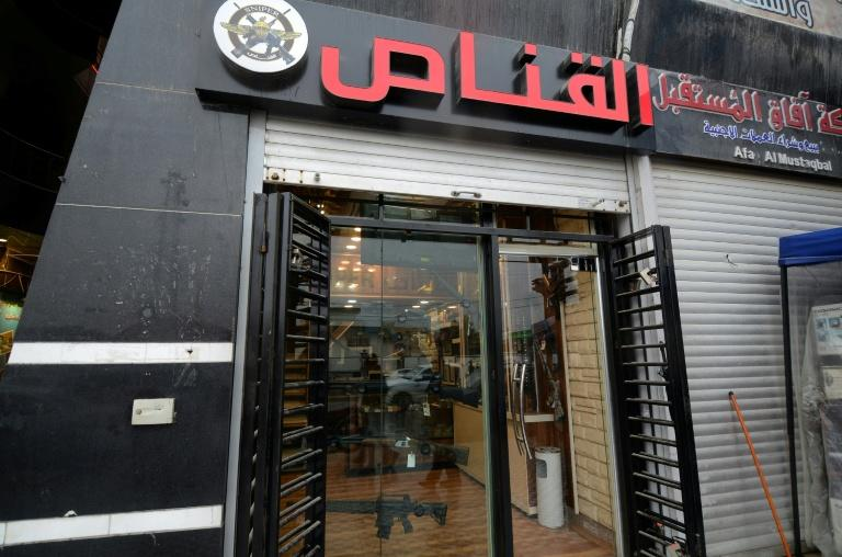 """Weapons are displayed in the window of a gunshop called """"The Sniper"""" in the northern Iraqi city of Mosul"""