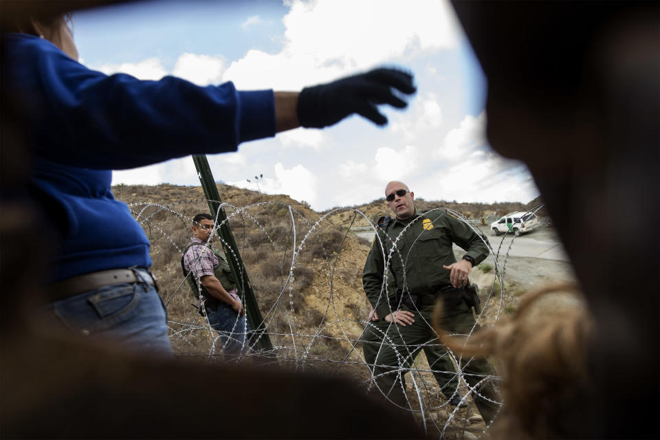 A US border police talk to migrants who entered in US territory through a hole in the border's wall on December 1, 2018. (Photo: Fabio Bucciarelli for Yahoo News)