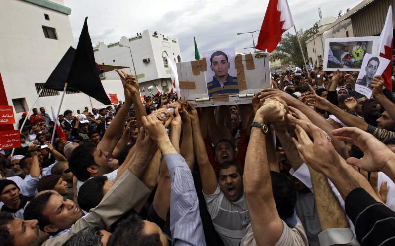 Bahrainis carry a coffin as they shout slogans during funeral of Ahmed Farhan, a 29-year-old demonstrator slain Tuesday in the town of Sitra, Bahrain, Friday, March 18, 2011. Thousands of Bahrainis gathered for the funeral of Ahmed Farhan, a 29-year-old demonstrator slain Tuesday in the town of Sitra hours after the king declared martial law in response to a month of escalating protests. Shiites account for 70 percent of the tiny island's half-million people but they are widely excluded from high-level posts and positions in the police and military. (AP Photo/Sergey Ponomarev)