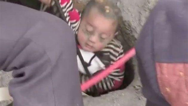 Video has captured the moment the tiny boy emerged from the earth after two hours underground with one arm raised above his head in a 'Superman'-like position. Photo: CCTV News
