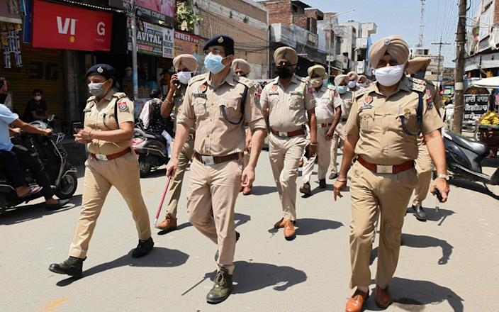 Indian police patrol through a market area in Amritsar to enforce the state's lockdown - Narinder Nanu/AFP