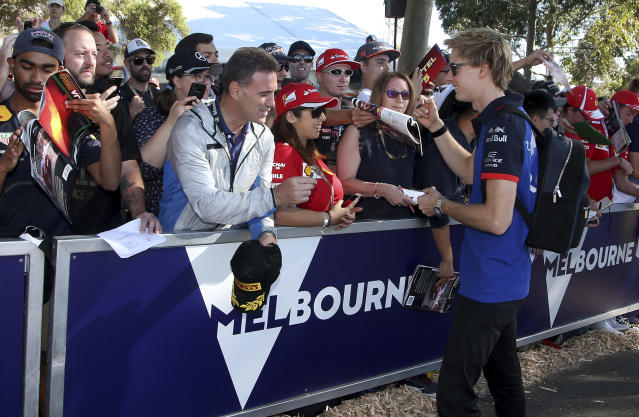 Toro Rosso driver Brendon Hartley, right, of New Zealand meets fans as he arrives at the track at the Australian Formula One Grand Prix in Melbourne, Friday, March 23, 2018. The first race of the 2018 seasons is on Sunday. (AP Photo/Rick Rycroft)