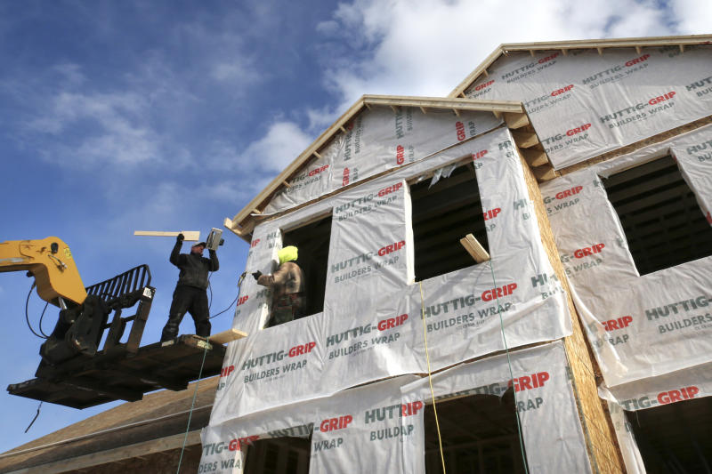 In this Feb. 20, 2020, photo a framing crew builds a home in Raymond, N.H. On Wednesday, Feb. 26, the Commerce Department reports on sales of new homes in January. (AP Photo/Charles Krupa)