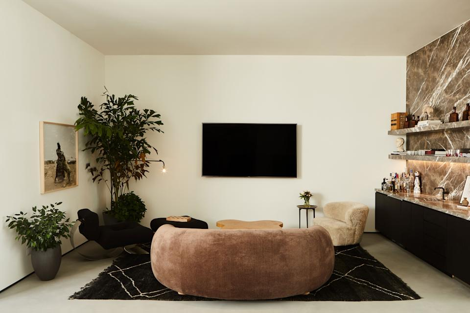 A chocolate-brown mohair sofa from JF Chen and the Cloud coffee table by Paul Frankl take center stage and sit on a vintage carpet from Marrakech. On the right, the custom bar in honed bronze vena stone is from Stoneland and the Danish 1940s Viggo Boesen–style lounge chair upholstered in cream shearling is next to a Rick Owens bronze side table. On the left, the Alta single armchair by Oscar Niemeyer combines with the Jean Prouvé Swing Jib lamp.