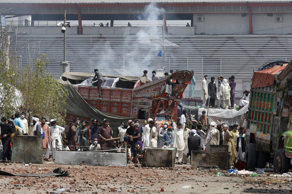 Supporters of Tehreek-e-Labiak Pakistan, a banned Islamist party, block a road and shout slogans protesting the arrest of their party leader Saad Rizvi, who was demanding the government to expel French ambassador, in Lahore, Pakistan, Sunday, April 18, 2021. A crackdown by security forces on protesting supporters of the banned party left several people dead and many others, including police officers, injured, a police spokesman said Sunday. (AP Photo/K.M. Chaudary)