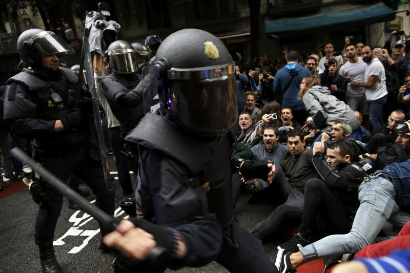 Spanish National Police tries to dislodge pro-referendum supporters sitting down on a street in Barcelona. (AP Photo/Manu Fernandez)