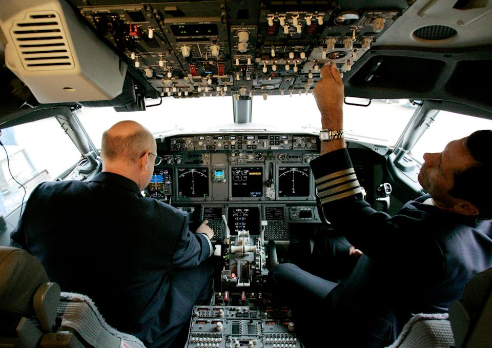 American Airlines pilots show the cockpit during a media preview of the Boeing 737-800 jets at Dallas Fort Worth International Airport in Grapevine, Texas in 2009. (Photo credit: AP Photo/Donna McWilliam, file)