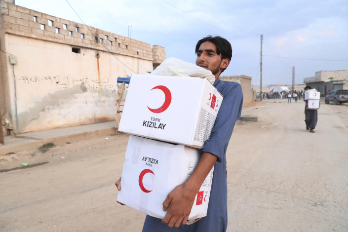 In this image provided by Turkish Red Crescent, a youth carries aid being distributed by Turkish Red Crescent in Ras Al-Ayn, Syria, Saturday, Oct. 19, 2019. Turkish Red Crescent says it has delivered humanitarian aid for 2000 people in Ras Al-Ayn, including flour with other food and hygiene materials to follow. The organisation said it also provided aid to Tal Abyad and will continue to do so in areas cleared by the Turkish and the Turkish-backed forces, from fighters from Kurdish People's Protection Units, or YPG. (Fatih Isci/Turkish Red Crescent via AP)