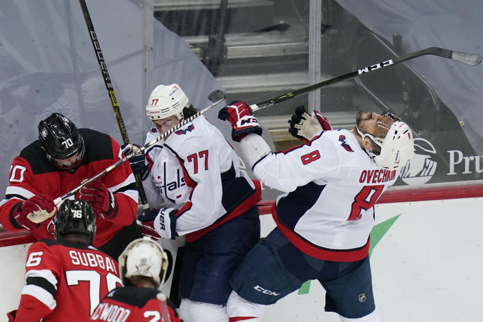 Washington Capitals' Alex Ovechkin (8) reacts after being hit with a high stick from New Jersey Devils' Dmitry Kulikov (70) during the second period of an NHL hockey game Sunday, April 4, 2021, in Newark, N.J. Kulikov was called for a penalty on the play. (AP Photo/Frank Franklin II)