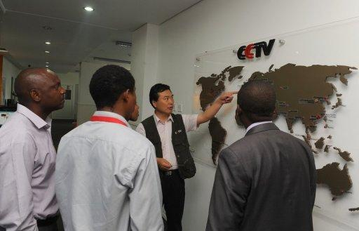 Pang Xinhua (2nd R), CCTV's managing editor who runs a network of correspondents in a dozen African countries, points to a map to show local correspondents how the organisation has expanded in different parts of Africa