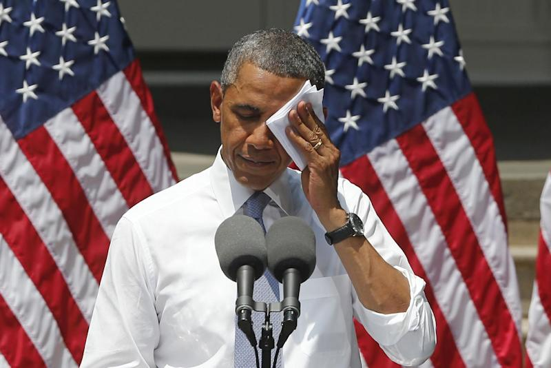 President Barack Obama wipes his face as he speaks about climate change, Tuesday, June 25, 2013, at Georgetown University in Washington. The president is proposing sweeping steps to limit heat-trapping pollution from coal-fired power plants and to boost renewable energy production on federal property, resorting to his executive powers to tackle climate change and sidestepping the partisan gridlock in Congress. (AP Photo/Charles Dharapak)