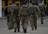 Members of the British armed forces 16 Air Assault Brigade walk to the air terminal after disembarking a Royal Airforce Voyager aircraft at Brize Norton