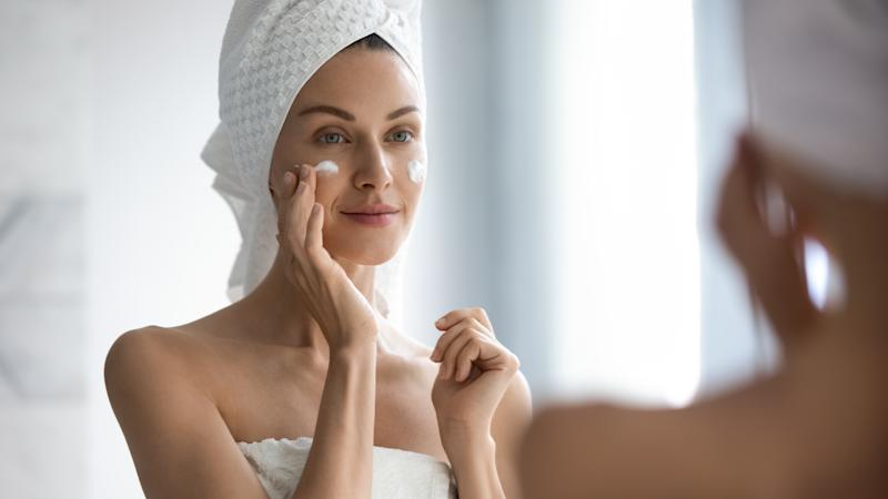 Attractive young adult woman apply facial cream look in mirror, beautiful healthy lady wrapped in towels put moisturizing lifting nourishing day creme on soft hydrated moisturized skin in bathroom