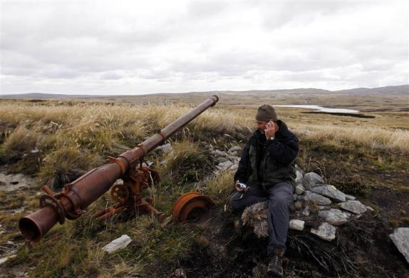 Argentine Falklands War veteran Marcelo Postonia talks on a cellular phone as he sits next to the cannon he used during the conflict near Port Stanley, March 12, 2012.