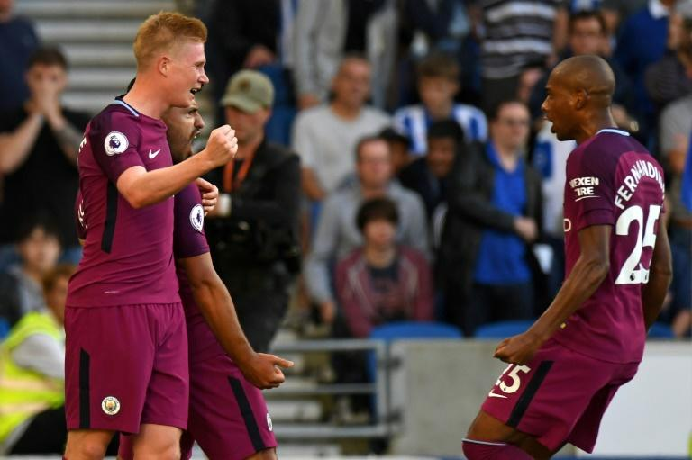 Manchester City's striker Sergio Aguero (2nd L) celebrates with midfielders Kevin De Bruyne (L) and Fernandinho (R) at the American Express Community Stadium in Brighton, southern England on August 12, 2017