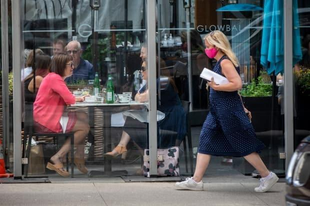 Diners are pictured eating at a restaurant in downtown Vancouver in June as a pedestrian passes wearing a face mask. (Ben Nelms/CBC - image credit)