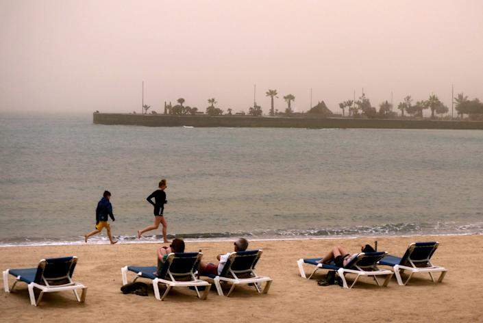 Children run along the beach as people look over the sea into the haze created by a sand storm known locally as
