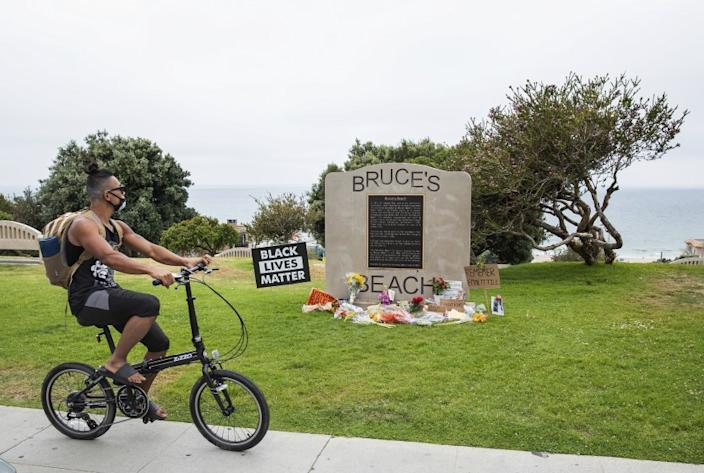 """A memorial to Emmett Till in front of a commemorative plaque at Bruce's Beach in Manhattan Beach on July 29. <span class=""""copyright"""">(Los Angeles Times)</span>"""