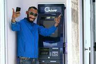 Special ATMs allow people to make bitcoin transactions and draw cash in dollars. This client is wearing a mask resembling President Nayib Bukele (AFP/MARVIN RECINOS)