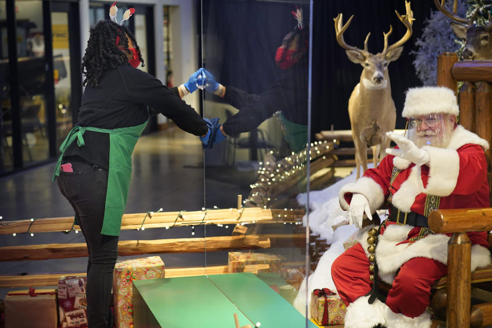 LaToya Booker cleans a transparent barrier between visitors for Santa at a Bass Pro Shop in Bridgeport, Conn., Tuesday, Nov. 10, 2020. Malls are doing all they can to keep the jolly old man safe from the coronavirus, including banning kids from sitting on his knee, completely changing what a Santa visit looks like. (AP Photo/Seth Wenig)