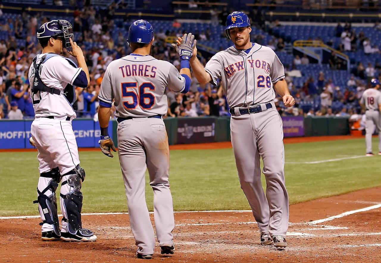 ST. PETERSBURG - JUNE 13:  Infielder Daniel Murphy #28 of the New York Mets is congratulated by teammate Andres Torres #56 after scoring against the Tampa Bay Rays during the game at Tropicana Field on June 13, 2012 in St. Petersburg, Florida.  (Photo by J. Meric/Getty Images)