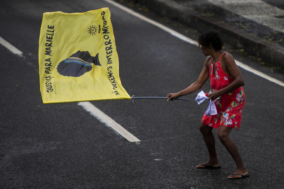 A woman holds a flag that reads in Portuguese