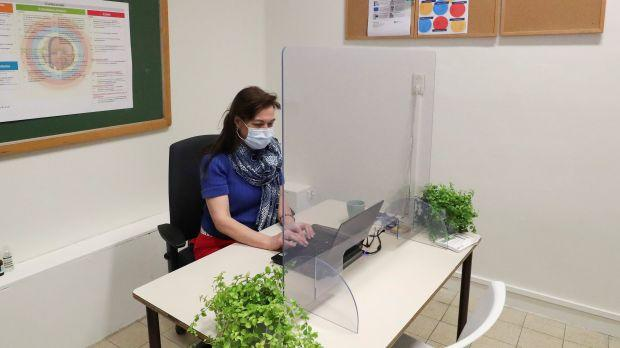 A staff member wearing a face mask sits in her office behind a protective plastic barrier at a flemish secondary school during its reopening in Brussels, as a small part of Belgian children head back to their schools with new rules and social distancing measures