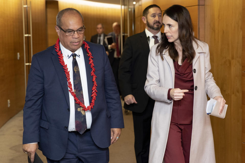 Pacific Peoples Minister Aupito William Sio, left, and Prime Minister Jacinda Ardern arrive for a post-Cabinet press conference at Parliament in Wellington, New Zealand, Monday, June 14, 2021. New Zealand's government is formally apologizing for an immigration crackdown nearly 50 years ago in which Pacific people were targeted for deportation, often after early-morning home raids. (Mark Mitchell/NZ Herald via AP)