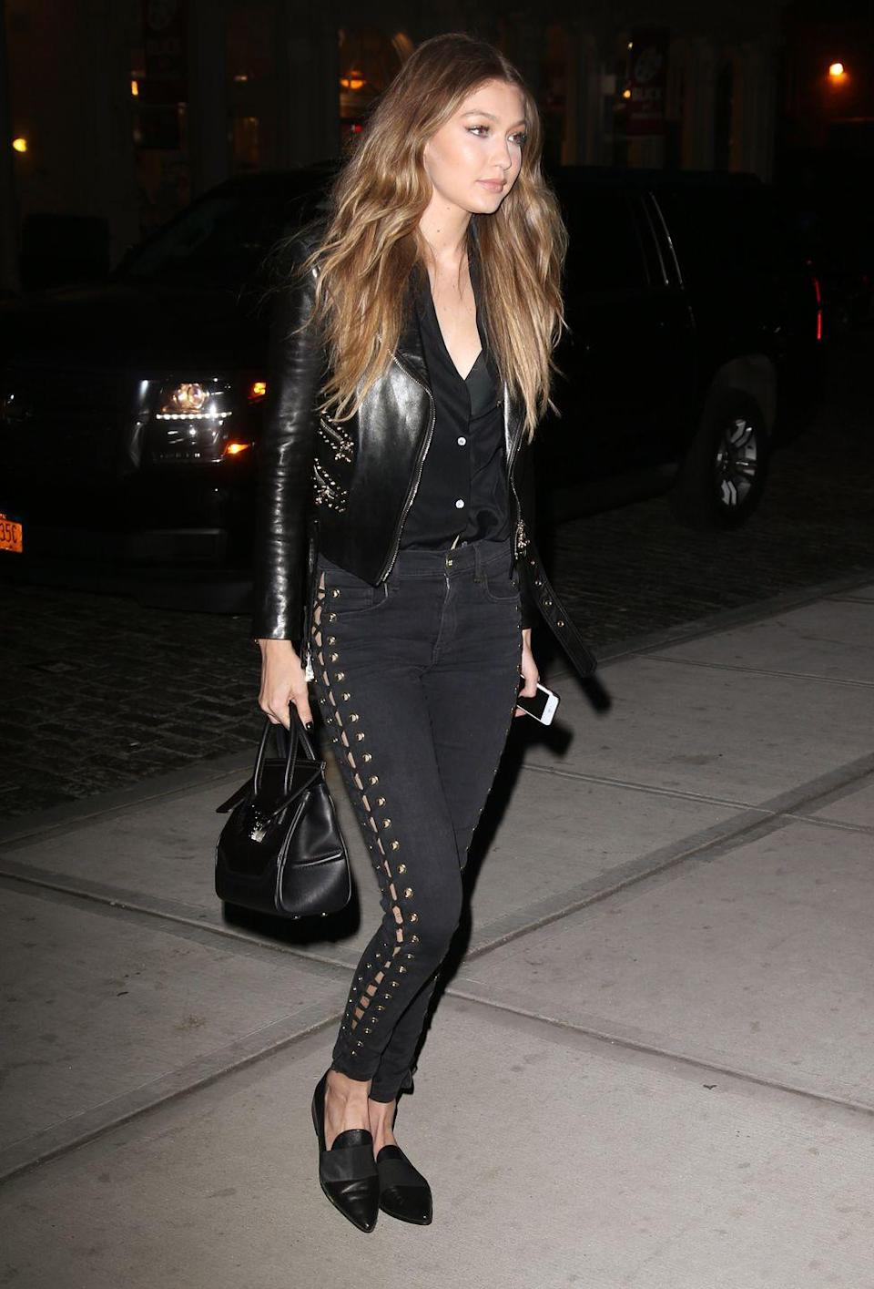 <p>The model stepped out in NYC wearing a Versace leather jacket and black jeans with lace-up detailing down the side, accessorized with a Versace bag and Stuart Weitzman loafers. </p>