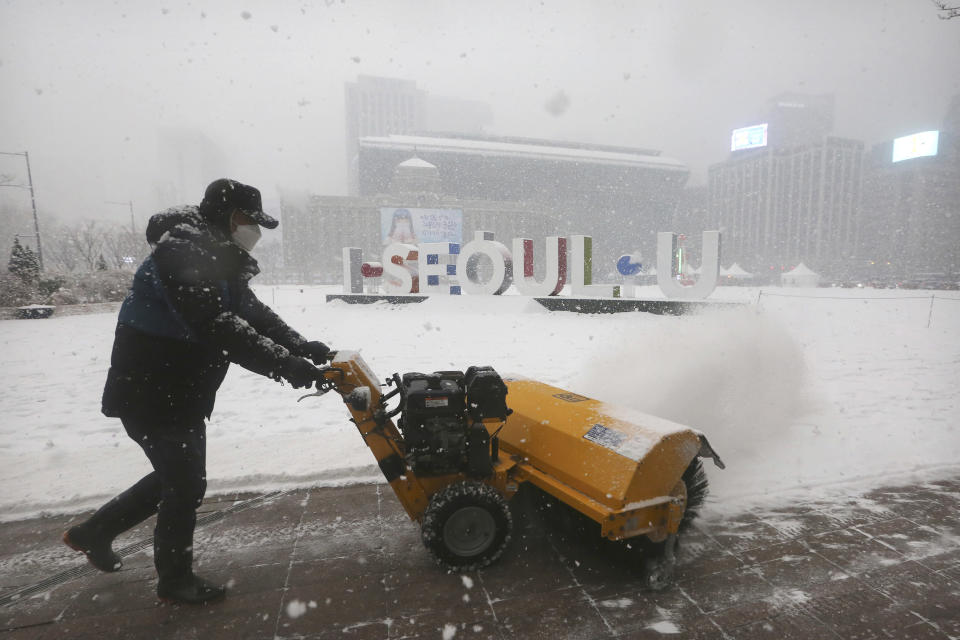 A worker wearing a face mask as a precaution against the coronavirus uses a snow blower to clear the sidewalks along City Hall Plaza in Seoul, South Korea, Tuesday, Jan. 12, 2021. (AP Photo/Ahn Young-joon)