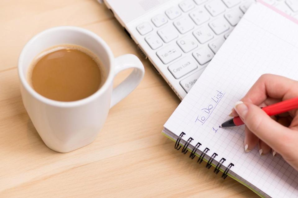 Woman writing a 'to do list' at her desk with a cup of fresh coffee