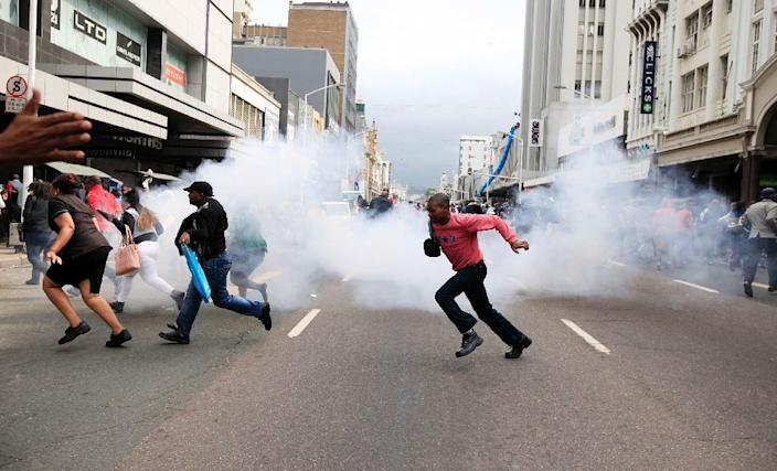 "People run for cover from a stun grenade and tear gas after a skirmish between locals and foreign nationals as thousands of people take part in the ""peace march"" against xenophobia in Durban, South Africa, on April 16, 2015 (AFP Photo/)"