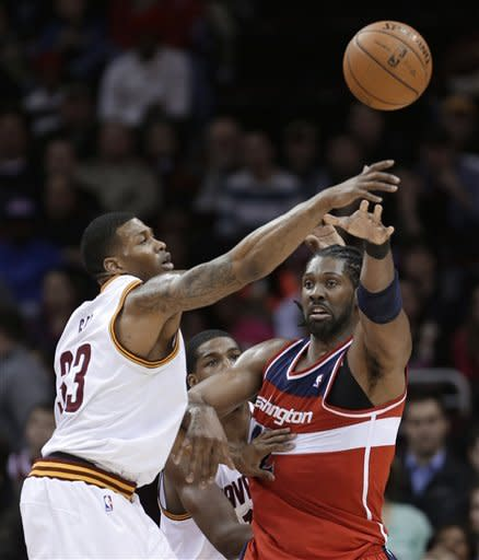 Washington Wizards' Nene, right, from Brazil, passes in front of Cleveland Cavaliers' Alonzo Gee (33) during the second quarter of an NBA basketball game Tuesday, March 12, 2013, in Cleveland. (AP Photo/Tony Dejak)