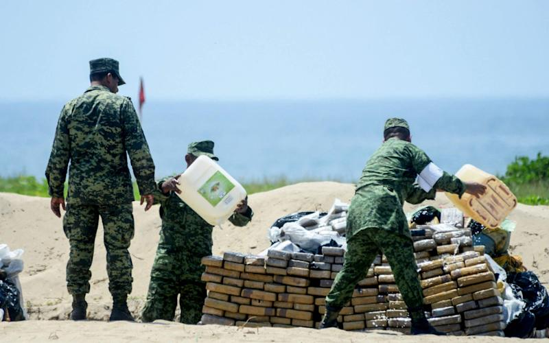 Mexican Navy and anti-narcotics personnel burn packs with part of a seizure of 5 tons of cocaine and marijuana - AFP