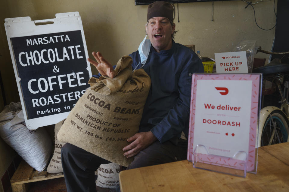 Jeffray Gardner, the owner of Marsatta Chocolate poses with a bag of cocoa beans at his company's office in Torrance, Calif., Sunday, March 28, 2021. Restaurants and delivery companies remain uneasy partners, haggling over fees and struggling to make the service profitable for themselves and each other. Gardner says he probably loses money on the one or two delivery orders he gets each day. But he's still happy to work with delivery companies because they help him reach a wider audience. (AP Photo/Damian Dovarganes)