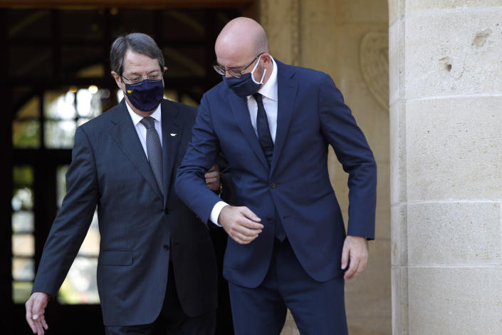 European Union Council President Charles Michel, right, is greeted by Cyprus President Nicos Anastasiades at the entrance of the Presidential Palace in the capital Nicosia, Cyprus, on Wednesday, Sept. 16, 2020. Michel is visiting Cyprus after traveling to Greece amid a diplomatic drive to de-escalate a weeks-long standoff at sea over Turkey's hydrocarbons search in waters were Greece and Cyprus claim exclusive economic rights. (AP Photo/Petros Karadjias)