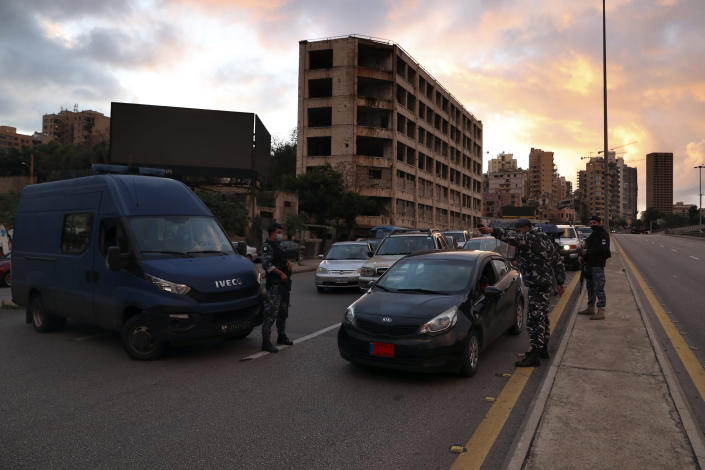 Police officers stand at a checkpoint to inspect cars that violate the lockdown during an 11-day nationwide shutdown aimed at curbing the spread of the coronavirus, in Beirut, Lebanon, Friday, Jan. 15, 2021. Lebanon's parliament has approved a draft law to allow the importing of vaccines into the tiny country to fight the spread of coronavirus. (AP Photo/Bilal Hussein)