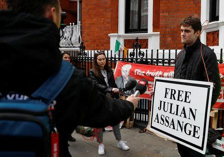 A supporter of WikiLeaks founder Julian Assange talks to the media, after Assange was arrested by British police, outside the Ecuadorian embassy in London, Britain, April 11, 2019. REUTERS/Peter Nicholls