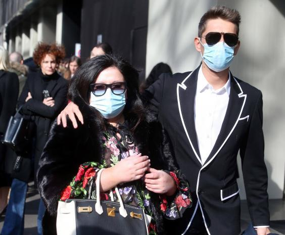 Guests wear face masks to protect against coronavirus upon arrival to attend the Dolce and Gabbana show during the Milan Fashion Week (EPA)