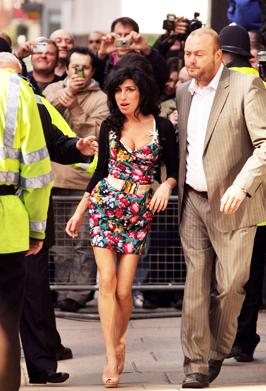 <p>Amy is escorted by her bodyguards from Westminster Magistrates Court in London, where she is in court for an assault charge of hitting a fan in 2008.</p>
