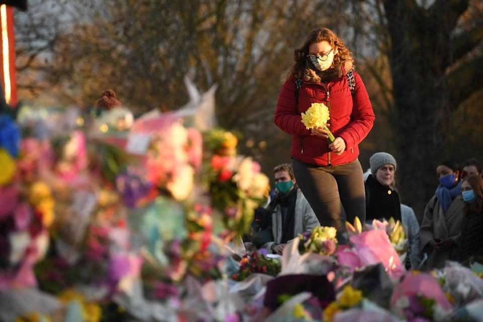 A woman places flowers in tribute to Sarah Everard, whose rape and murder by off-duty police officer Wayne Couzens in March, sparked the report (Victoria Jones/PA) (PA Archive)
