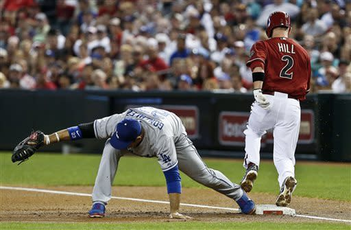 Los Angeles Dodgers' Adrian Gonzalez, left, reaches out to catch a ball to get Arizona Diamondbacks' Aaron Hill (2) out at first base during the first inning in a baseball game, on Sunday, April 14, 2013 in Phoenix. (AP Photo/Ross D. Franklin)
