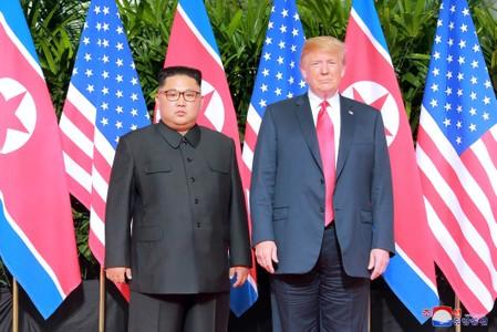 FILE PHOTO:  U.S. President Donald Trump and North Korean leader Kim Jong Un pose at the Capella Hotel on Sentosa island in Singapore