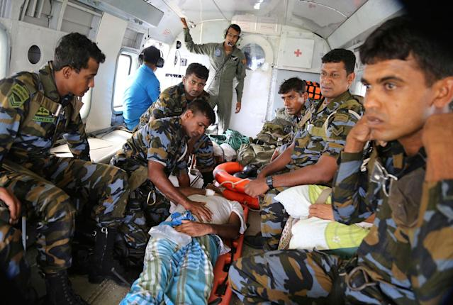 <p>Sri Lankan air force personnel attend to a flood victim inside a helicopter after rescuing him in Kalawana, in Ratnapura district of Sri Lanka, May 27, 2017. (AP Photo/Rukmal Gamage) </p>
