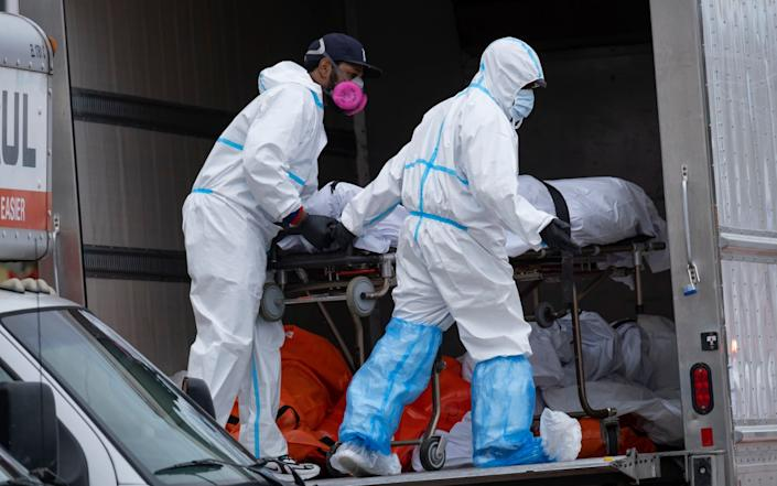 Workers move bodies to a refrigerated truck from the Andrew T. Cleckley Funeral Home - AP