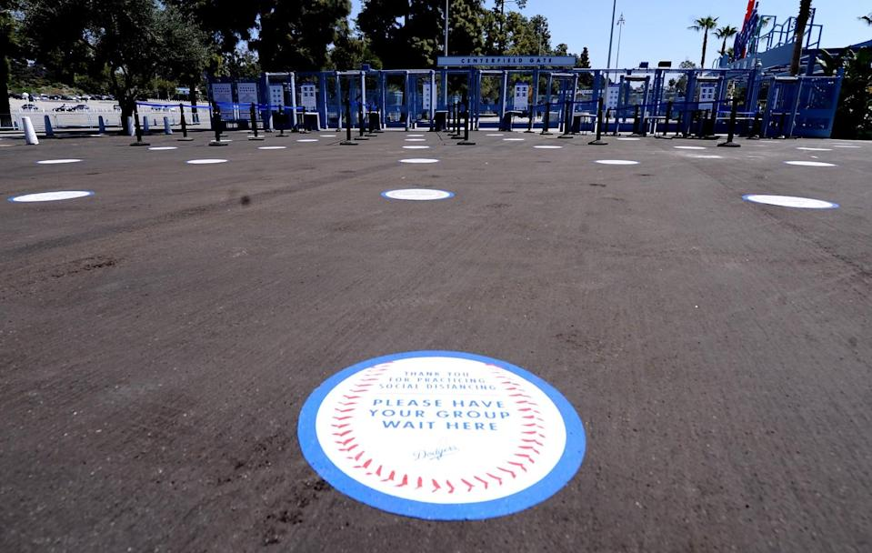 Markings for where fans should stand are placed on the ground outside the center field gate.