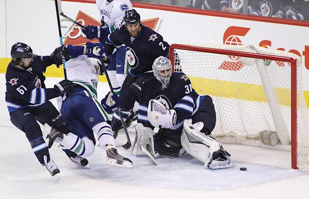 WINNIPEG, MB - APRIL 4: Michael Frolik #67 of the Winnipeg Jets puts pressure on Chris Higgins #20 of the Vancouver Canucks as Ondrej Pavelec #31 manages to get the puck out of the net during third period action in an NHL game at the MTS Centre on April 4, 2015 in Winnipeg, Manitoba, Canada. (Photo by Marianne Helm/Getty Images)