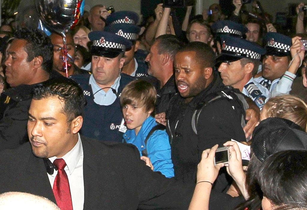"""Spot the Bieber! The fandemonium continued for tween sensation Justin Bieber Tuesday as he arrived at Auckland Airport. With overzealous teenage girls threatening to squash the pint-sized pop star in their attempts to get near him, 16-year-old JBiebs needed a police escort to get to his car. <a href=""""http://www.splashnewsonline.com"""" target=""""new"""">Splash News</a> - April 27, 2010"""
