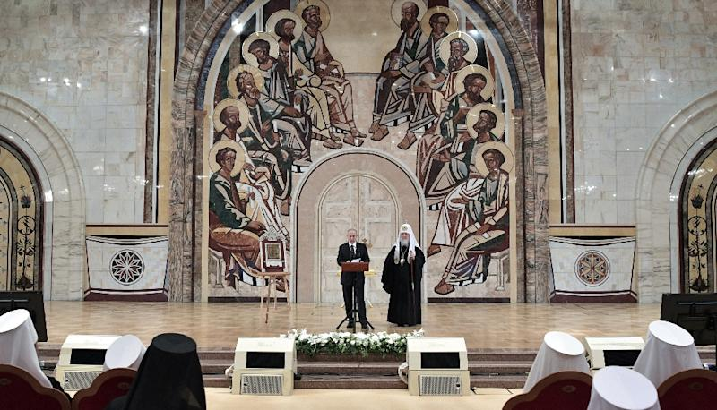 Russian President Vladimir Putin, accompanied by Patriarch Kirill, at a congress of Orthodox bishops at Moscow's Cathedral of Christ the Saviour (AFP Photo/Alexey NIKOLSKY)